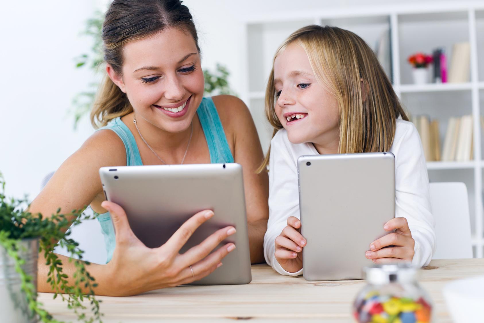 Mutter und Tochter spielen mit Tablets