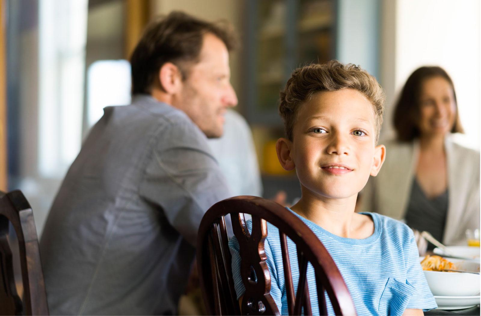 Junge sitzt auf einem Stuhl, im Hintergrund sind seinem Eltern am Tisch