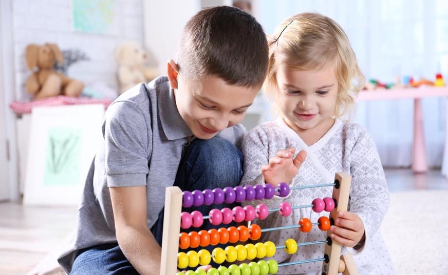 Ein Junge und ein Mädchen spielen mit einem Rechenschieber