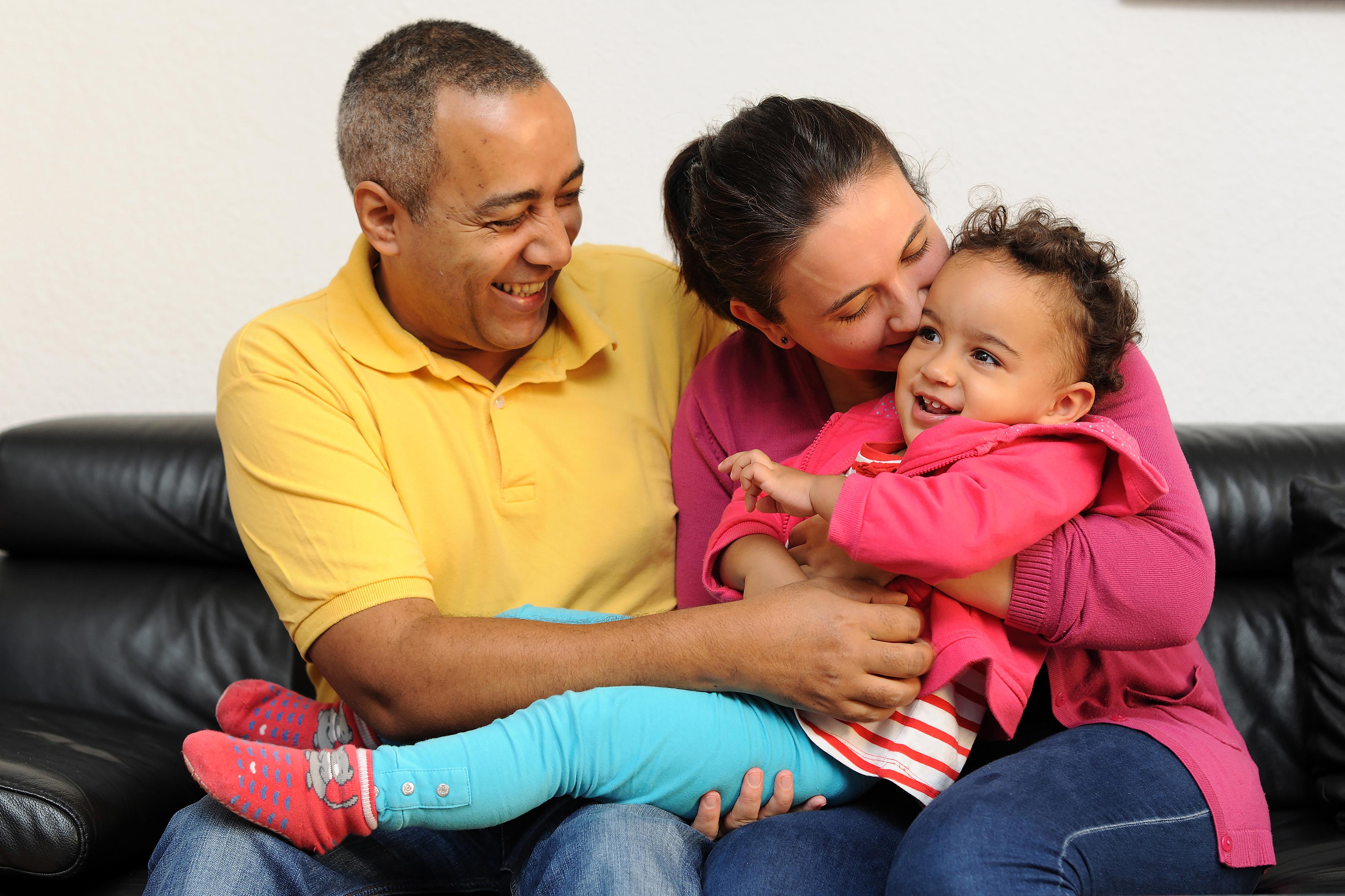Mutter, Vater und Kind in liebevoller Umarmung auf eine Couc