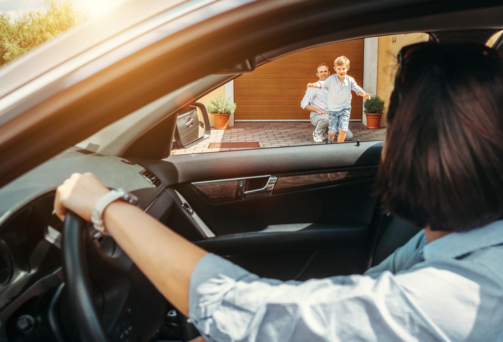 Mutter sitzt im Auto, Sohn läuft auf sie zu, Vater im Hintergrund