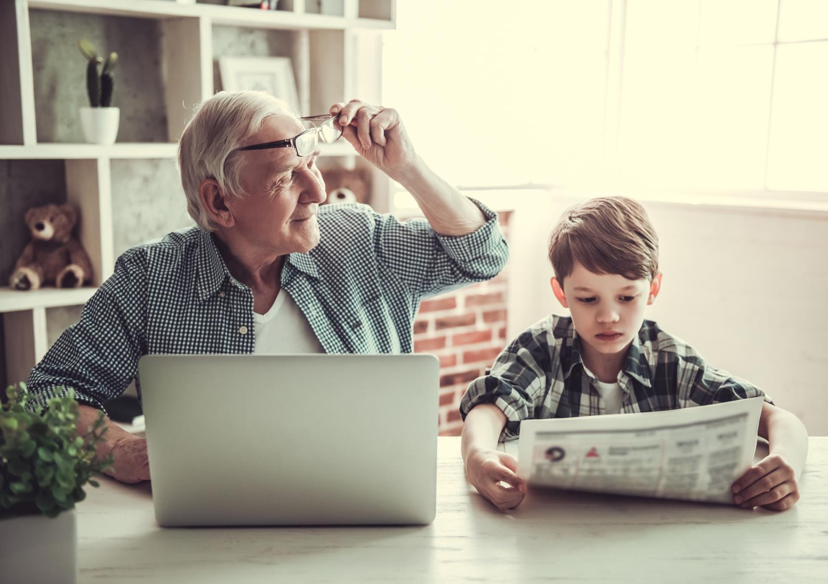 Ein Großvater mit Laptop und sein Enkel mit Zeitung sitzen gemeinsam am Tisch