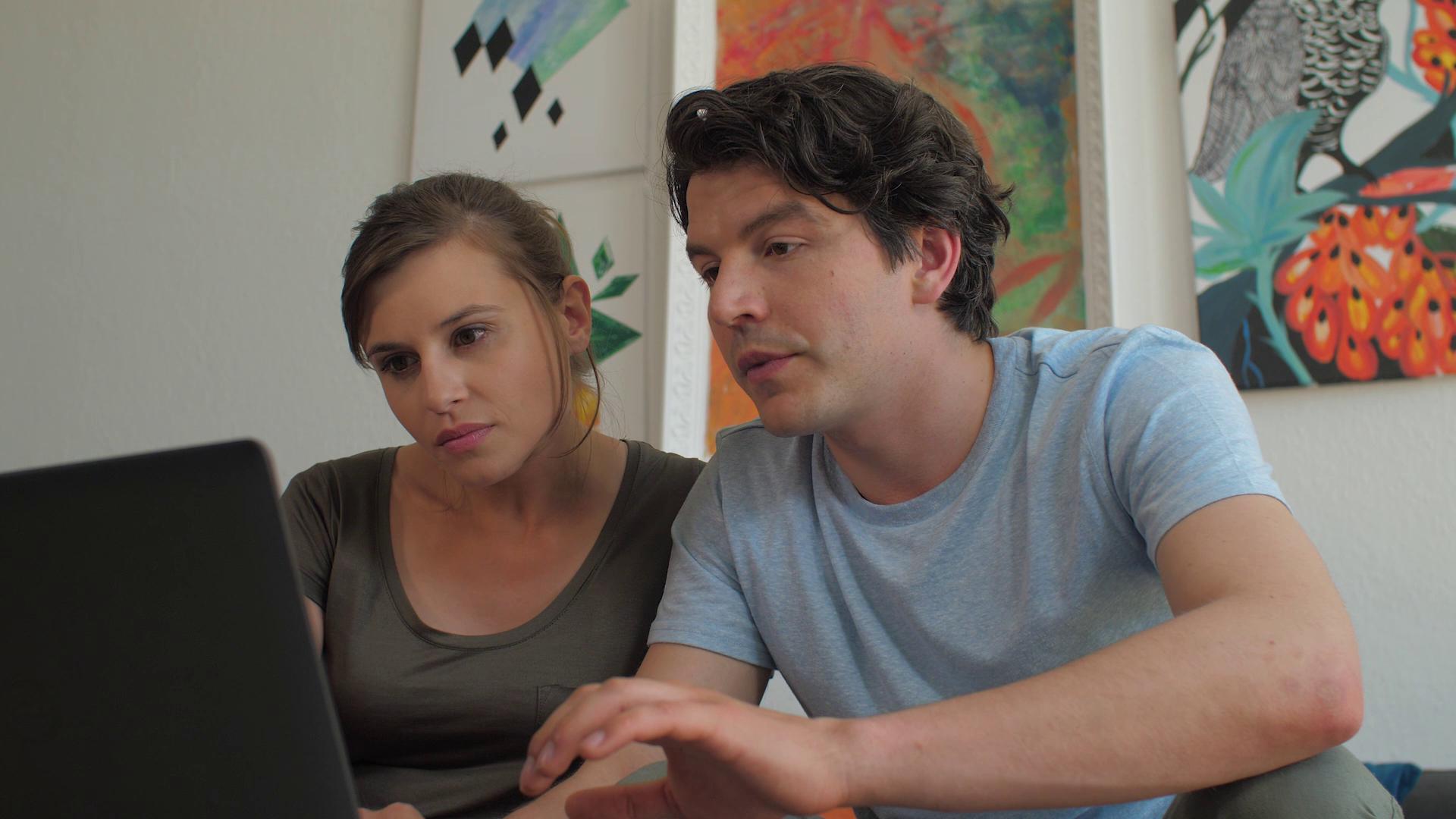 Ein Paar sitzt an einem Laptop