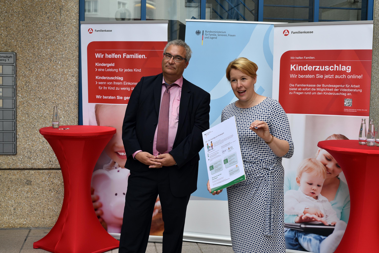 Dr. Franziska Giffy und Karsten Bunk vor Aufstellern zum Thema Kinderzuschlag und Kindergeld der Familienkasse