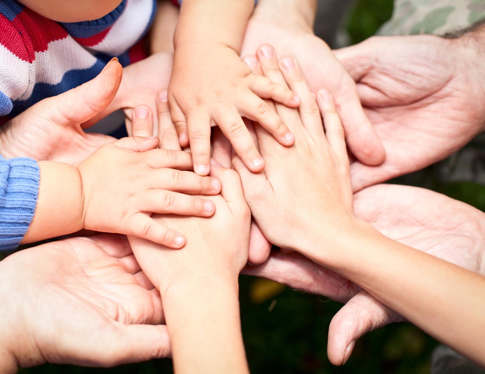Auf dem Bild sind Hände von Kindern und Erwachsenen zu sehen