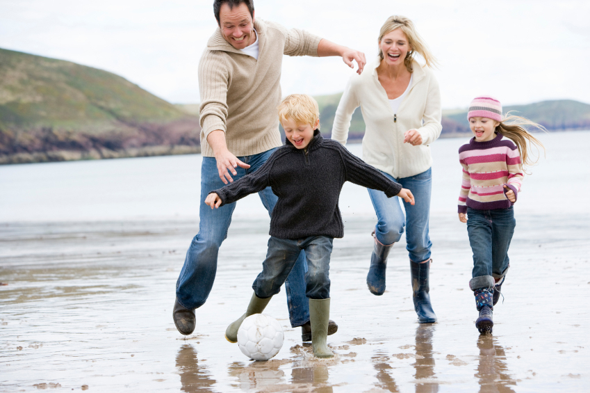 Porträt einer spielenden Familie am Strand
