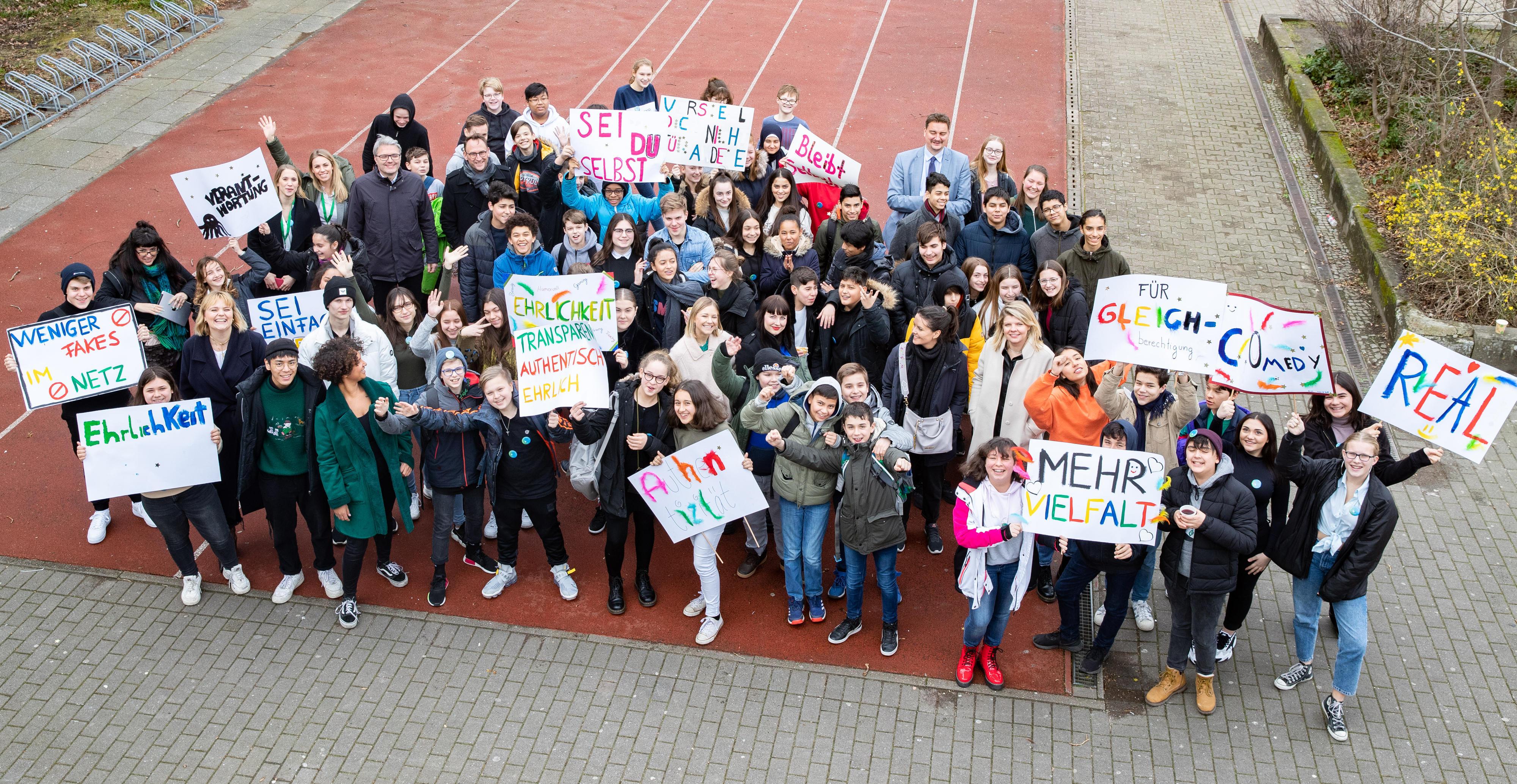 Eine Gruppe von Jugendlichen hält Transparente zu mehr Ehrlichkeit und Vielfalt hoch