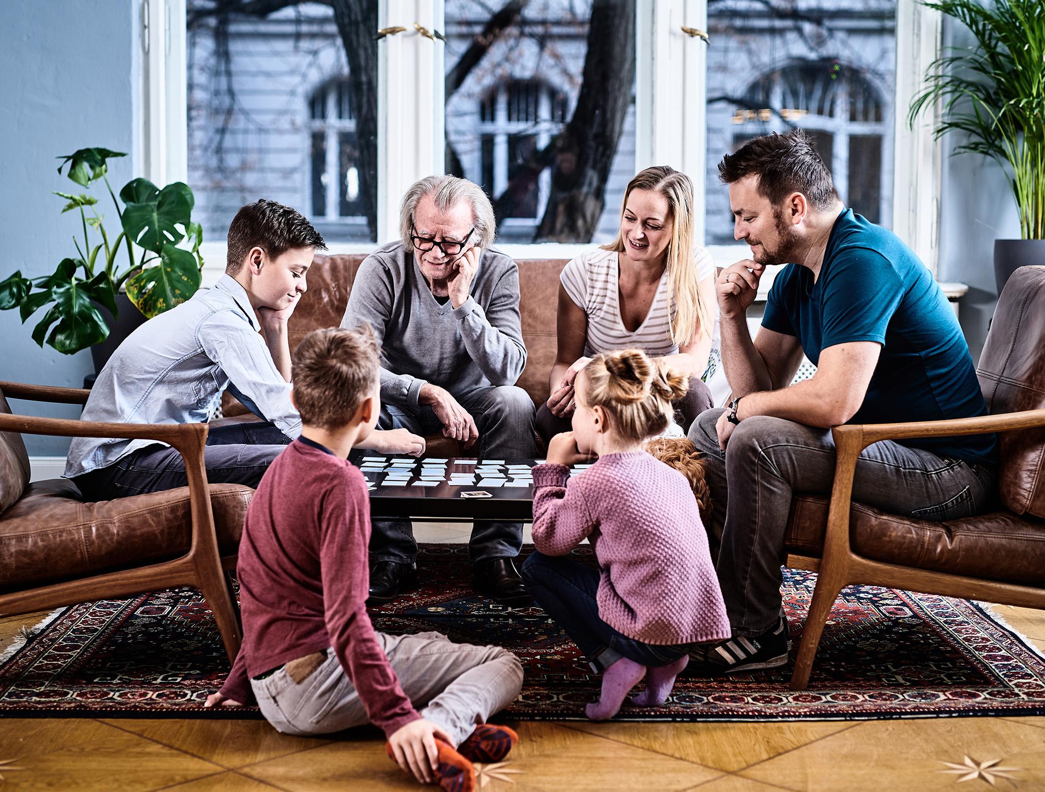 Eine Familie sitzt am Tisch und spielt