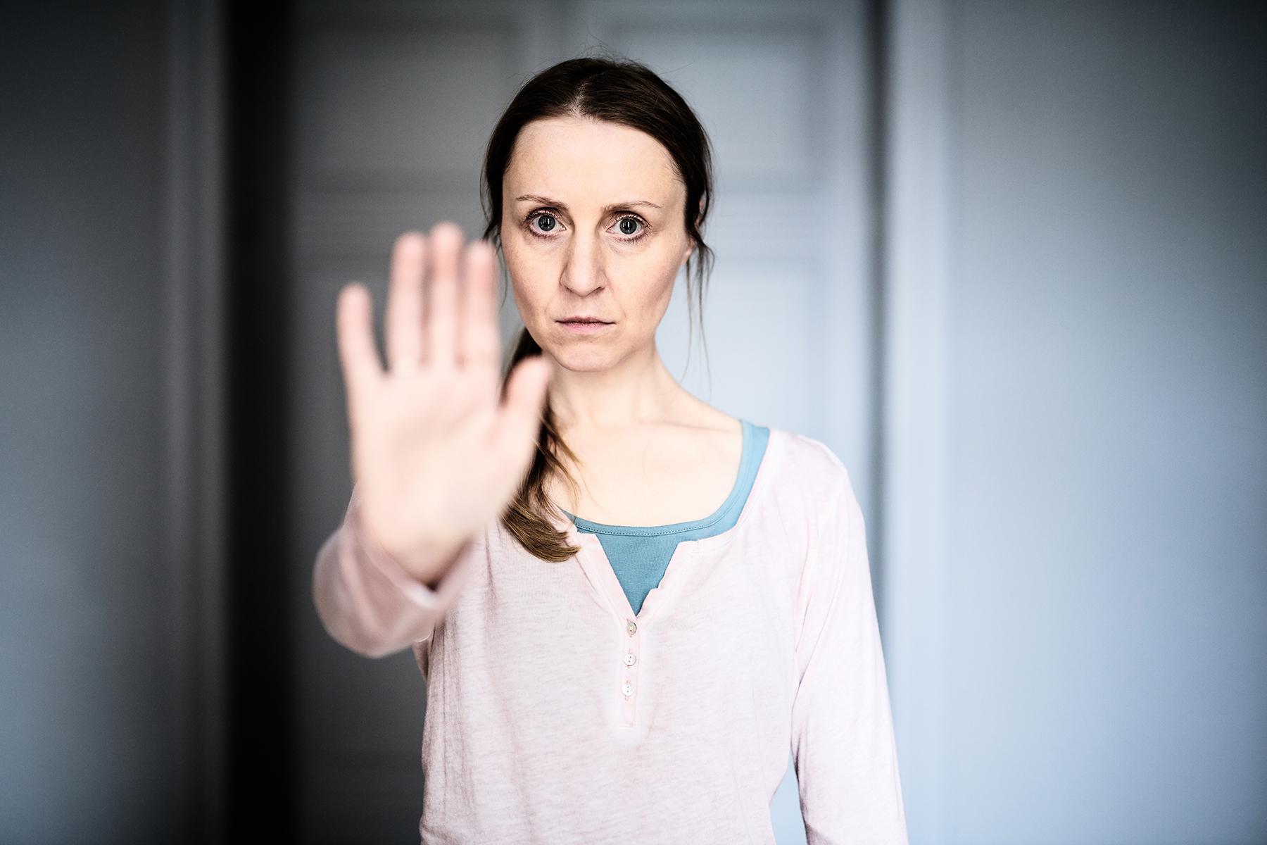 """Eine Frau hebt die Hand und sagt """"stopp"""""""