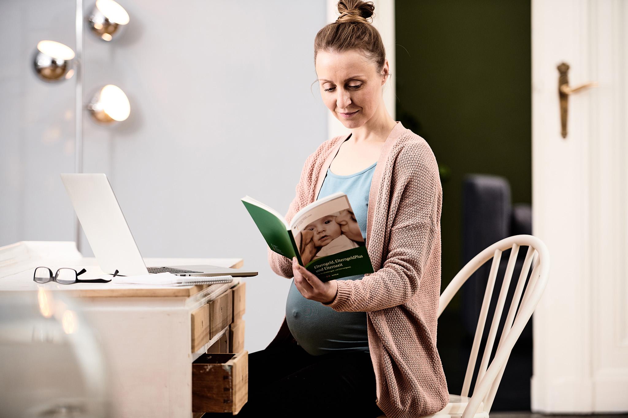 Eine schwangere Frau blättert in einer Broschüre