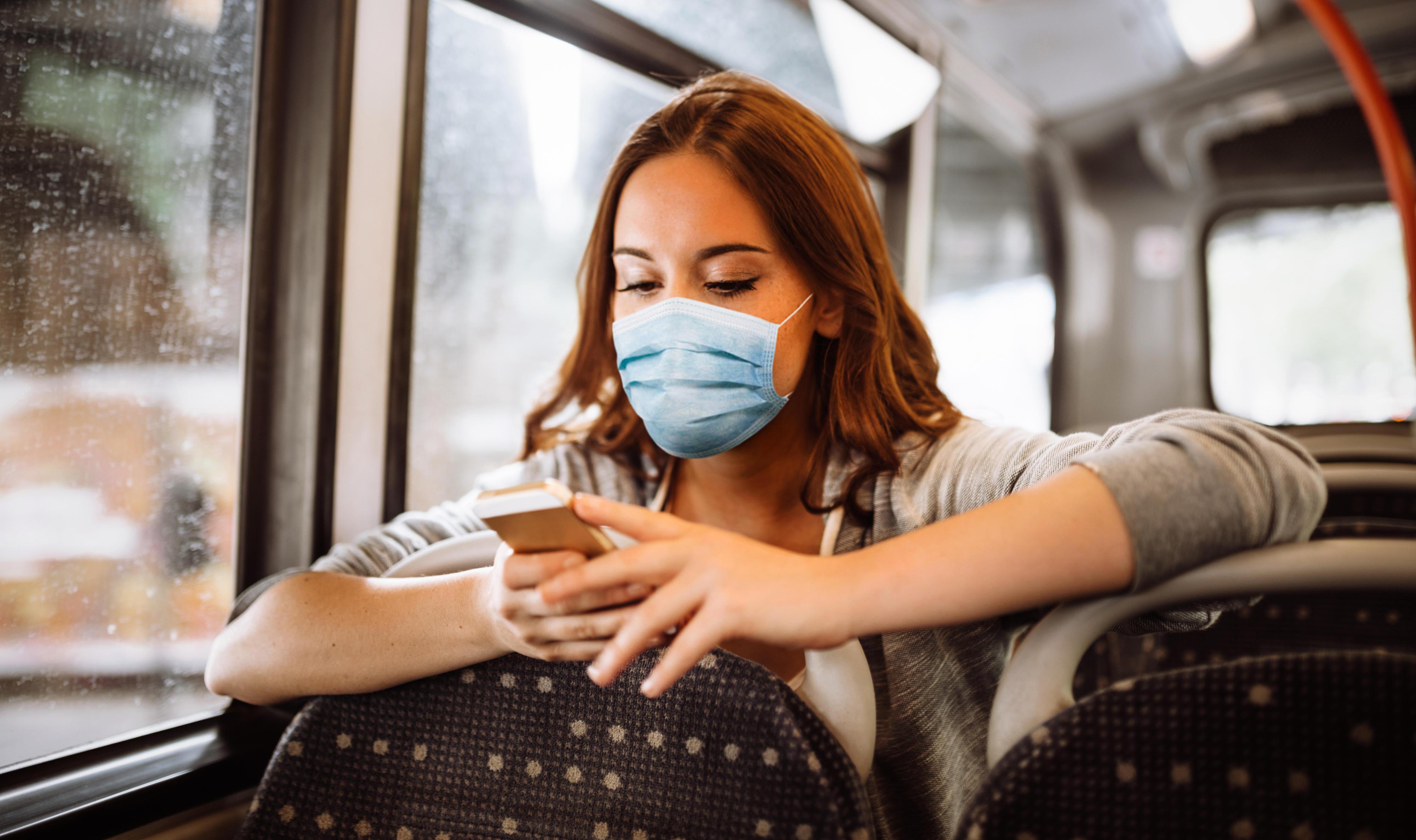Eine junge Frau mit Mundschutz und Smartphone im Bus