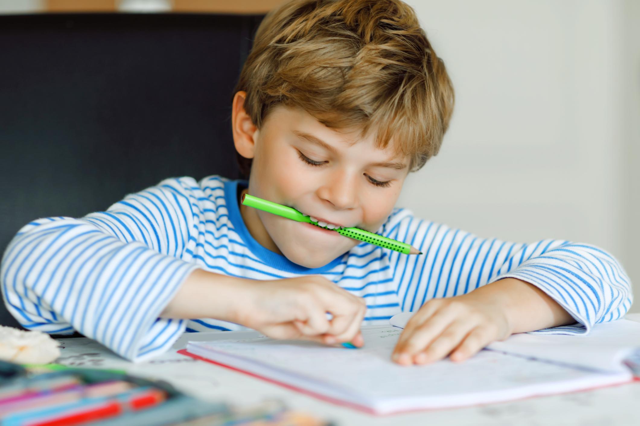 Schulkind am Tisch macht Haushaufgaben