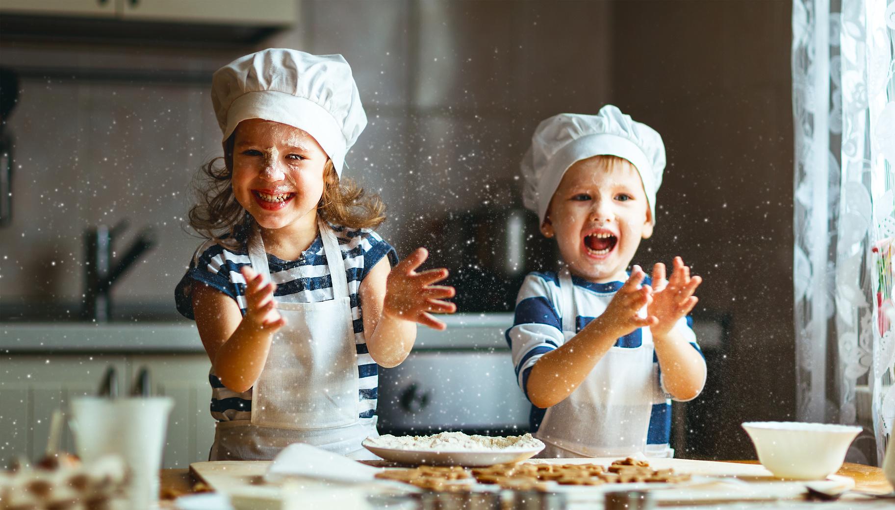 2 Kinder mit Backmützen in einer Küche backen Waffeln und freuen sich