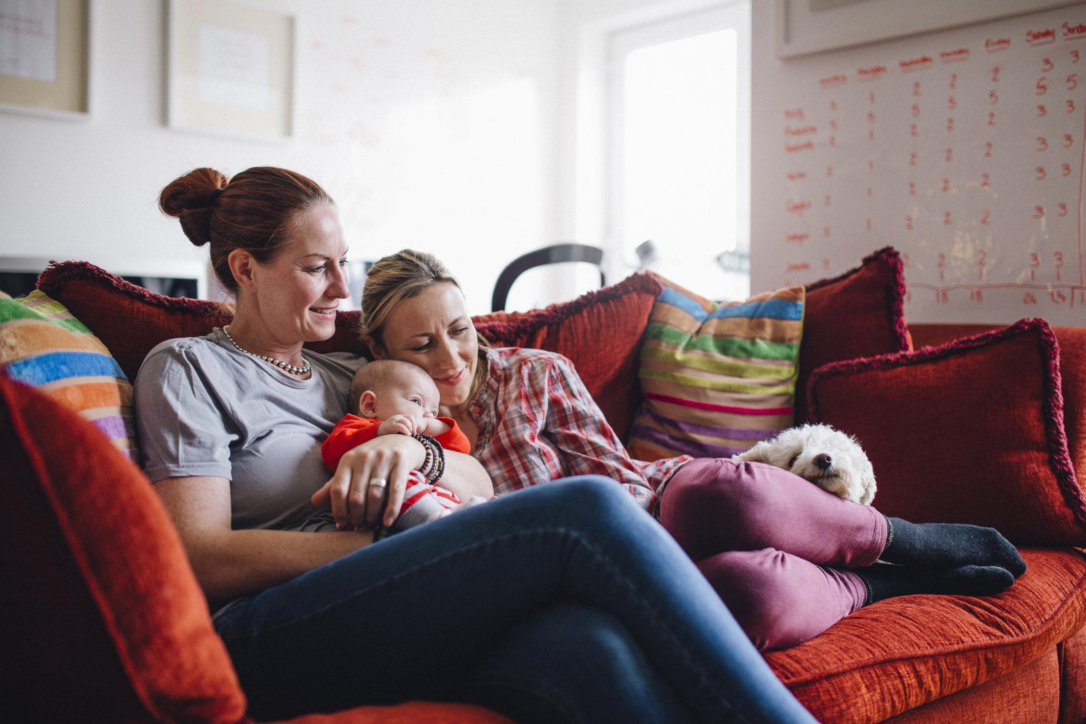 Zwei Mütter auf einer Couch mit einem Baby