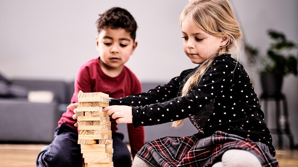 Zwei Kinder spielen zusammen in einem Wohnzimmer