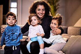 Eine Mutter sitzt mit ihren drei Kindern auf einer Coach
